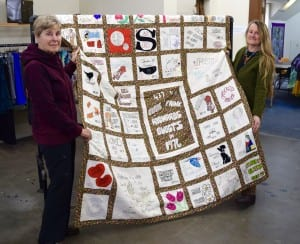 Jeni Cottrell and Lee Cole holding a quilt made by Elsie Richards capturing stories from over 400 visitors in one summer.